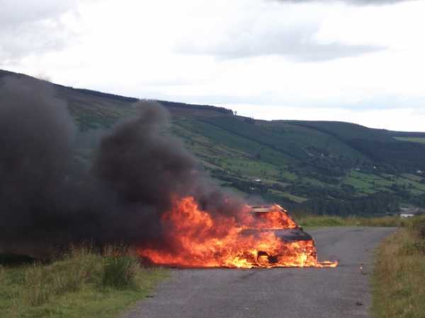 """Car ablaze with slopes of Seahan Mountain behind"" from wicklore Contract pics"