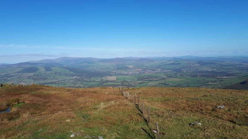 View North-East from near the summit: Lugnaquilla at the left;  with Croghanmoira (centre left) and Ballinacor (centre right) as backdrop to Aughrim in the valley below
